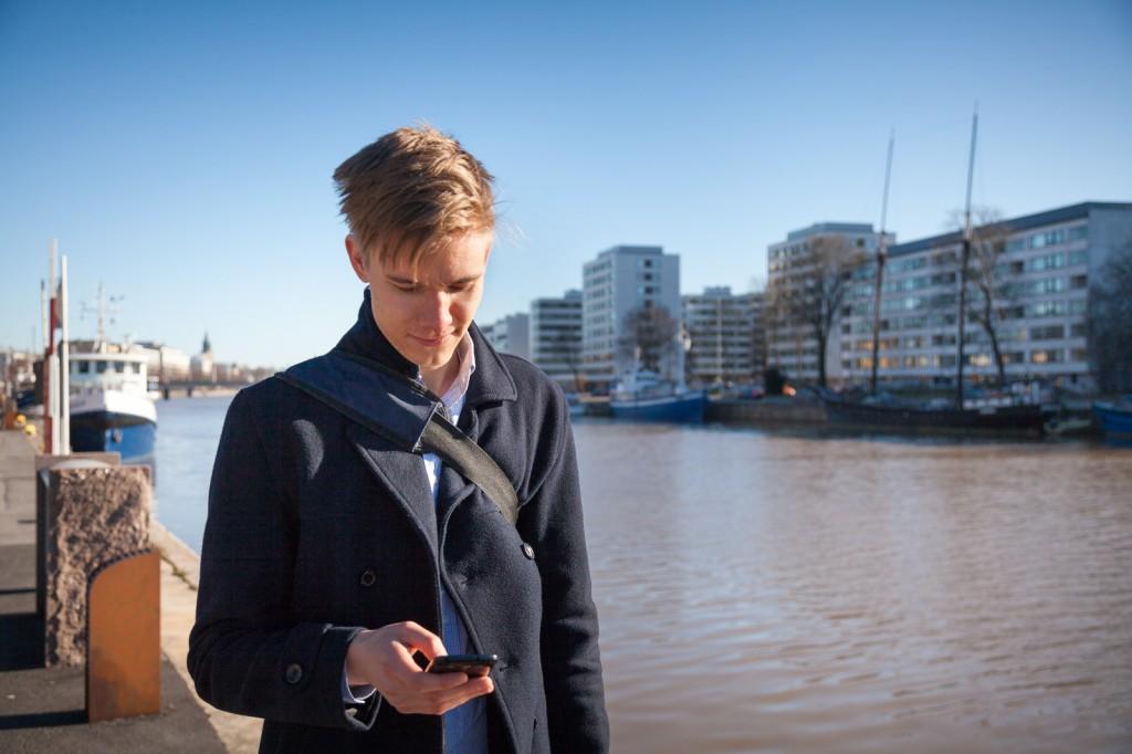 Mobiilikäyttäjä joen varrella