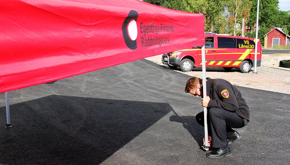 Päivystävät palotarkastajat hoitavat tehtäväänsä muiden töiden ohessa. Kuvassa Janne Aso Saariston turvallisuuspäivillä Iniössä pystyttämässä valistustelttaa.
