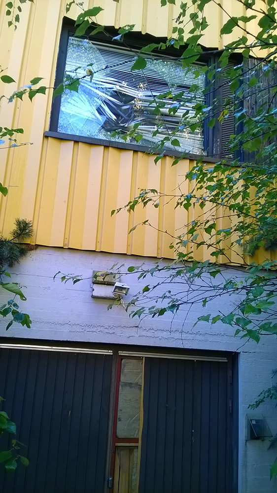 Lapset ja nuoret kulkivat ovesta, jonka yläpuolella ikkunassa tuuli heilutti isoja lasinkappaleita.