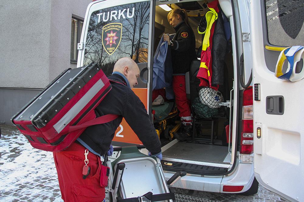 Kaksi ensihoitajaa valmistelemassa ambulanssia lähtöön talvella asuinrakennuksen pihalla.