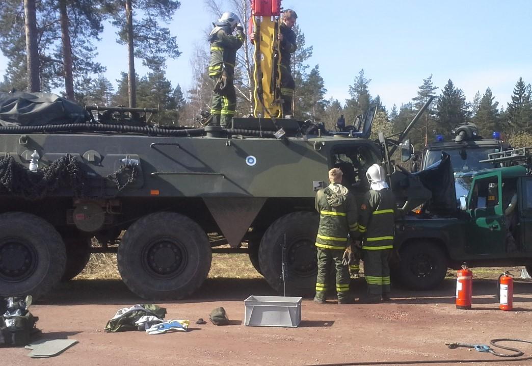 Kuvassa on armeijan ajoneuvo ja henkilöitä sen läheisyydessä.
