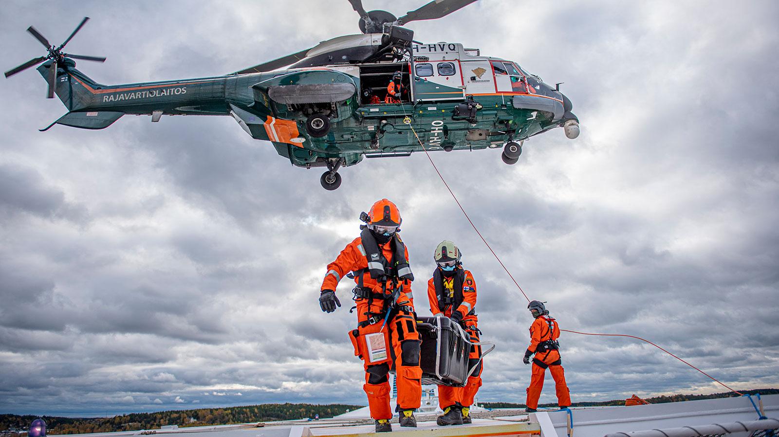MIRG-miehistöä kantamassa laatikkoa laivan kannella. Taustalla helikopteri.