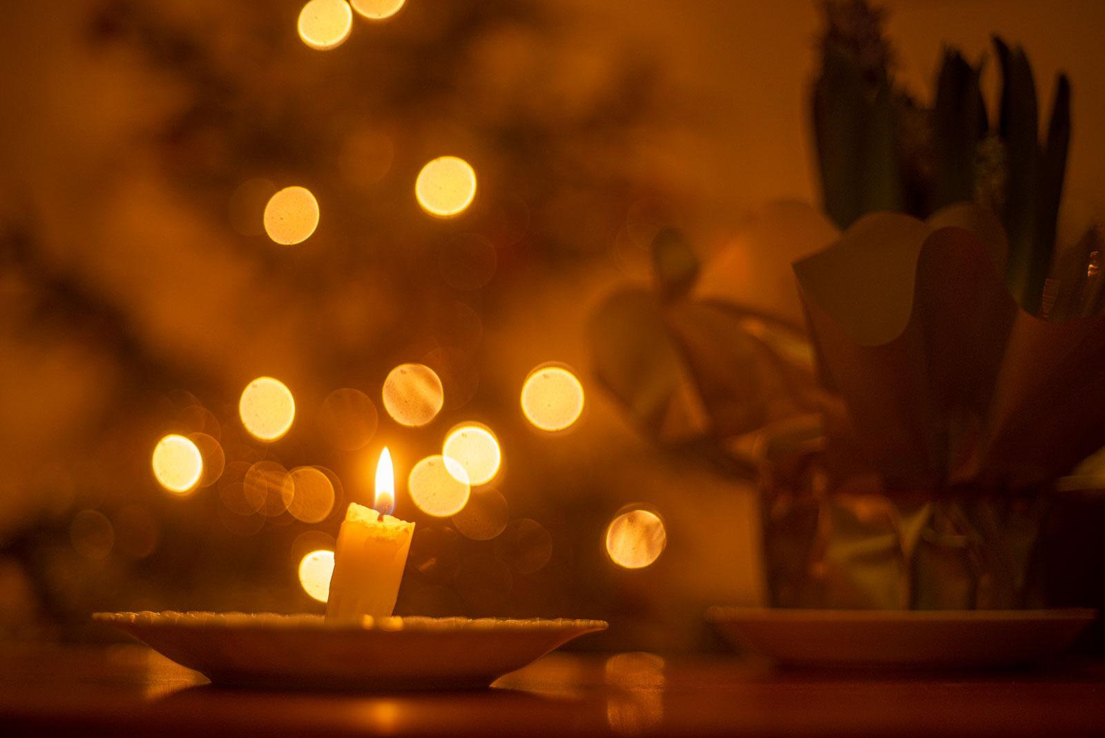 kuvassa on kynttilä ja taustalla joulukuusi